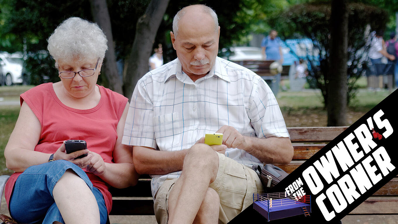 boomers on bench looking at phones