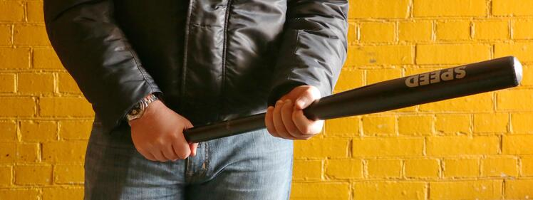 man in leather jacket holding a baseball bat